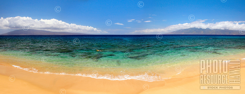 A snorkler swimming at Airport Beach in West Maui, with Moloka'i and Lana'i in the distance.
