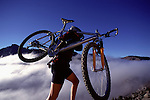 A photo of a woman mountain biker carrying her bike above a sea of clouds in the Sierra mountains.