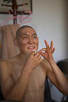 """Martial artist Zheng Xuejin does his make up in the manager's office of Red Theatre. """"Chun Yi: The Legend of Kungfu"""" is an entertaining piece of drama, which has been showing for consecutive five years in Beijing, China."""