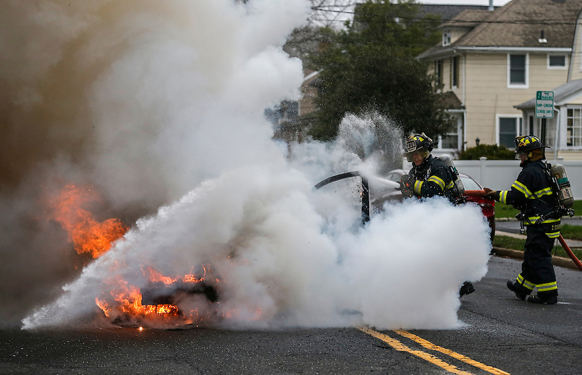 MANASQUAN, NJ — April 1, 2016 —Manasquan firefighters Kevin McCredie and Tom Schofield douse a 2000 Ford Focus that was fully engulfed in flames at about 9:40am on Broad Street, here. The driver of the vehicle, Nancy Trapani, was not injured.  photo by Andrew Mills