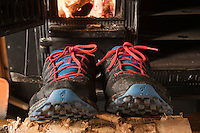 Tral running shoes dry outside wood burning stove at Sälka hut after wet day of hiking, Kungsleden trail, Lapland, Sweden