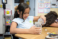 Alice Feng '20 and Alexandra Pfleegor '20 (glasses) present. Second grader Kaely Magdaleno pours different liquids into jars as part of a Boundless Brilliance demonstration.<br /> Occidental students give presentations on STEM (science, technology, engineering, and mathematics) to students at Buchanan Street Elementary School in the Highland Park area of Los Angeles, Calif., March 8, 2018.<br /> In 30-minute presentations to kindergarten to sixth-grade students, Boundless Brilliance's teams of college students, all women currently attending Occidental, go into classrooms to create excitement about science. Through simple experiments (such as building a bridge between two chairs using only newspapers and tape) and a message couched in confidence, respect, and teamwork, their message to everyone—and young girls in particular—is simple: You are brilliant and you can be a scientist if you want to be.<br /> (Photo by Marc Campos, Occidental College Photographer)