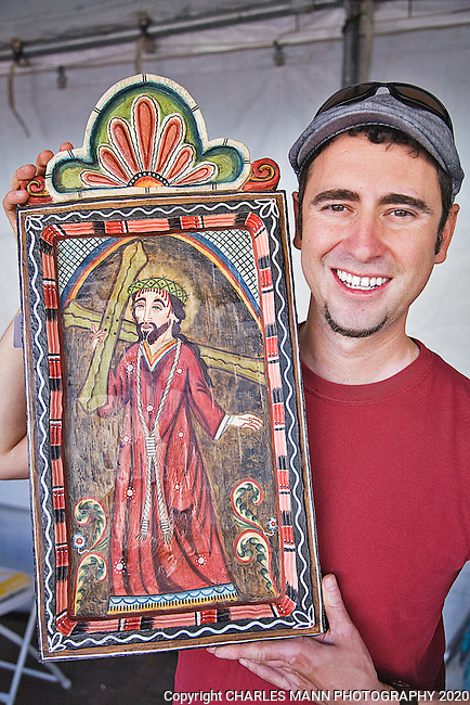 The Santa Fe Spanish Market, held in late July, fills the Santa Fe Plaza with artists, patrons and visitors all celebrating the richness of the Spanish Colonial art tradition side by side with the Contemporary Spanish Art Market. Artist James M. Cordova holds his prize wining retablo, a painting on a woooden tablet.