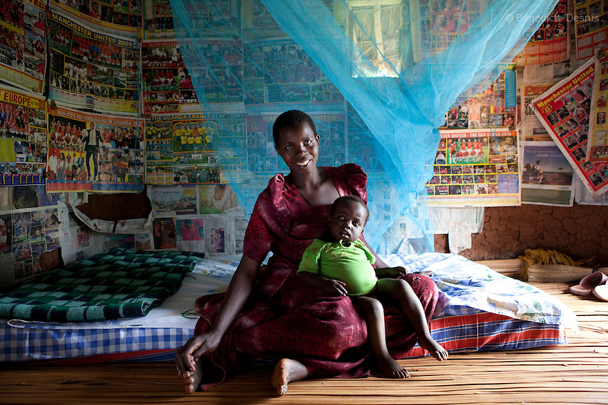 15 april 2010  Busagazi, Uganda - Florence Tibiita and her son sit on their bed with a mosquito net used for preventing malaria. Malaria is a mosquito-borne infectious disease. The disease kills over a million people in the world every year, mostly children and pregnant women. Malaria transmission can be reduced preventing mosquito bites by using mosquito nets and insect repellents, or by mosquito-control measures such as spraying insecticides inside houses and draining standing water where mosquitoes lay their eggs. Photo credit: Benedicte Desrus
