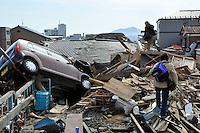 KMA35 KESENNUMA (JAPÓN) 14/03/2011.- Una pareja de ancianos camina entre los escombros en dirección a su casa en Kesennuma, prefectura de Miyagi (Japón) hoy, lunes 14 de marzo de 2011. Un total de 1.833 personas murieron y otras 2.369 se encuentran desaparecidas a causa del grave seísmo de 9 grados en la escala Richter sucedido el viernes y posterior tsumani, de acuerdo con el último recuento policial. EFE/Kimimasa Mayama.