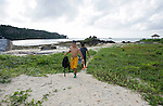 Young locals walk on the beach after snorkeling on the reef near the municipal beach at Onna Village, Okinawa Prefecture, Japan, on Saturday, June 23, 2012. Photographer: Robert Gilhooly