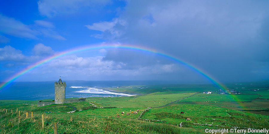 County Clare, Ireland<br /> Rainbow arches over tower castle near Doolin, Ireland's west coast