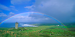 County Clare, Ireland<br /> Rainbow arches over tower castle near Doolin, Ireland's west coast