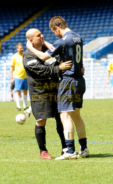 HASSAN & DANNY DYER .Celebrity Soccer Six in aid of The Samaritans held at Chelsea Football ground, Stamford Bridge, London, England..May 24th 2009 .football match game full length blue top shorts socks black holding head hands hug embrace profile .CAP/FIN.©Steve Finn/Capital Pictures.