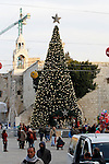 Palestinians walk past a Christmas tree at the Manger Square near the Church of the Nativity, revered as the site of Jesus Christ's birth, on December 22, 2016 in the biblical West Bank town of Bethlehem. Photo by Wisam Hashlamoun
