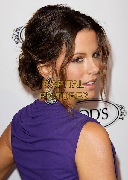 KATE BECKINSALE.The Diego Della Valle Cocktail Celebration Honoring Tod's Beverly Hills Boutique And MOCA's New Director Jerry Deitch at Tod's Boutique in Beverly Hills, California, USA..headshot portrait hair up earrings starburst dangly purple cowel neck make-up looking over shoulder .CAP/RKE/DVS.©DVS/RockinExposures/Capital Pictures.
