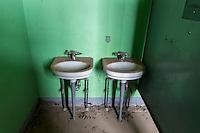 Bathroom sinks inside an abandoned school in Park, KS