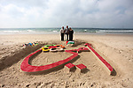 """Palestinian artist Mohammed Totah with amputated leg, poses with his parents in front a sand sculpture reads in Arabic """"my mother"""" to mark the Mother's Day, at the beach of Gaza city on March 21, 2019. Totah, 31 year-old, who had lost his leg during the Israeli war on Gaza Strip in 2008, despite his disability, he succeeded in writing and drawing sculptures by sand on the Gaza beach marking the national events. Photo by Mahmoud Ajjour"""