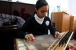 "FOR FAOIROUZ SONG ""THE FLOWER OF THE CITIES"" - A Palestinian girl plays the Kanoun during a lesson in the Edward Said National Conservatory of Music in East Jerusalem. Photo by Quique Kierszenbaum."