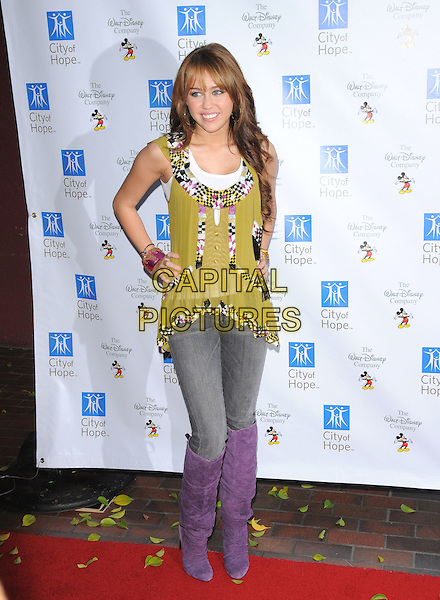 MILEY CYRUS .At Disney's Concert for Hope, a benefit concert supporting City of Hope cancer research and treatment programs held at Universal Ampitheatre in Universal City, California, USA..September 14th, 2008.full length jeans denim tucked into purple boots green yellow pattern top hands on hips .CAP/DVS.©Debbie VanStory/Capital Pictures.