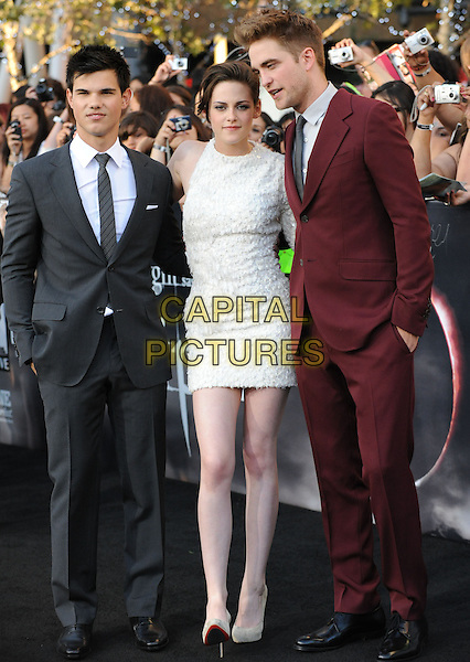 TAYLOR LAUTNER, KRISTEN STEWART & ROBERT PATTINSON.The premiere of The Twilight Saga : Eclipse held at the Los Angeles Film Festival at Nokia Live in Los Angeles, California, USA..June 24th, 2010    .full length suit shirt tie grey gray white black red maroon burgundy suit black grey gray shirt beige shoes hand in pocket dress couple one sleeve.CAP/RKE/DVS.©DVS/RockinExposures/Capital Pictures.