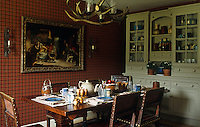 The dining room has walls of dark red tartan with a large dresser at one end and an antler chandelier above the table