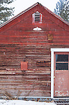 Snow falls on a rustic, weather-beaten red barn out in the country.