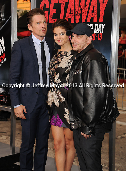 WESTWOOD, CA- AUGUST 26: Actors Ethan Hawke (L), Selena Gomez (C) and director Courtney Solomon arrive at the 'Getaway' - Los Angeles Premiere at Regency Village Theatre on August 26, 2013 in Westwood, California.