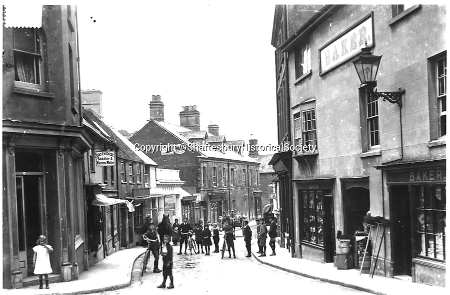 BNPS.co.uk (01202 558833)<br /> Pic: ShaftesburyHistoricalSociety/BNPS<br /> <br /> Pictured: The high street pictured today. Claire Ryley, of the Shaftesbury and District Historical Societ said, 'It is fascinating to see how the high street looked at a time when people took precedence over cars' <br /> <br /> These charming photos reveal everyday life at the turn of the 20th century in a thriving market town later made famous by a TV advert.<br /> <br /> The black and white snapshots of Shaftesbury, Dorset, were taken by Albert Tyler who set up a photography business there in 1901.<br /> <br /> There are various street scenes and also images of the locals in traditional attire, with men in flatcaps and women in bonnets.<br /> <br /> Tyler photographed the busy opening of the town market in 1902, and a garden party where men played croquet.