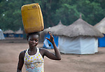 A woman carries water in a camp for internally displaced persons that formed around the Our Lady of Assumption Catholic Church in Riimenze, South Sudan. The parish has provided food, shelter material, and health care, and the presence of the local priest and a group of religious has contributed to a sense of relative safety.