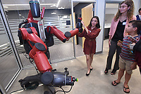 NWA Democrat-Gazette/FLIP PUTTHOFF <br /> Abby Lopez, a student at Bentonville West High School, shows guests on Wednesday how Baxter the robot works during the opening of Ignite professional studies program in Bentonville. Ignite students hone their skills in a number of career fields.
