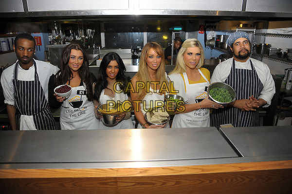 Lauren Goodger, Peri Sinclair, Lauren Pope, Frankie Essex .The Live Below The Line celebrity charity cook-off, Shoreditch Waterhouse restaurant, Orsman Rd., London, England..March 5th, 2012.half length white apron yellow beige top food bowl kitchen.CAP/CAS.©Bob Cass/Capital Pictures.