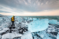 Photographer at Diamond Beach, icebergs at the black lava beach, near glacier lagoon Jökulsarlon, Vatnajökull National Park, Hornafjörður, Southern Iceland, Iceland