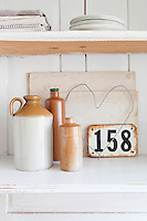 A collection of flasks and other treasures is stored in the vintage kitchen cupboard
