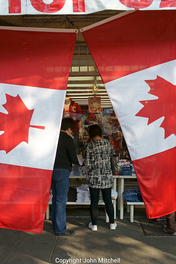 Shoppers framed by a pair of Canadian flags, Chinatown, Vancouver, British Columbia, Canada