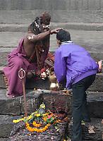 Pashupatinath, Nepal.  Sadhu (Holy Man) at Nepal's Holiest Hindu Temple Blessing a Worshiper.