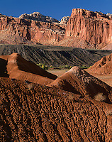 Capitol Reef National Park, UT<br /> View of eroded badlands along the Scenic Drive with the Fremont River Valley and red cliffs of Capitol Reef in the distance