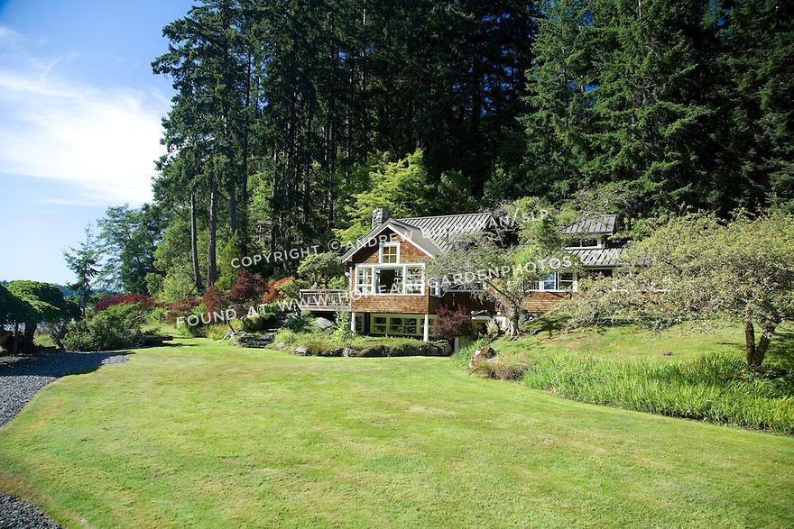 A wood-shingled waterfront weekend vacation retreat sits amid towering evergreen trees on Washington State's Vashon Island.