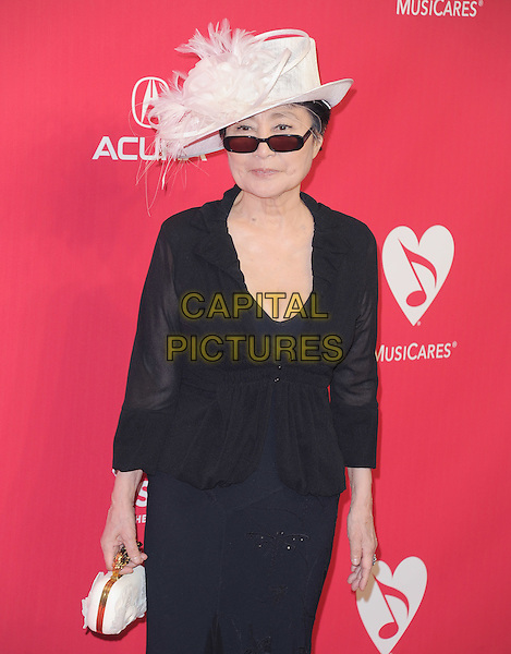 Yoko Ono.at The 2012 MusiCares Person of the Year Dinner at the Los Angeles Convention Center, West Hall in Los Angeles, California, USA, .February 10th 2011..half length black hat sunglasses white feather cream feathers top clutch bag knuckle dusters .CAP/RKE/DVS.©DVS/RockinExposures/Capital Pictures.
