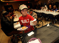 NWA Media/ANDY SHUPE - Reid Slagle, 8, of Rogers collects plates and utensils while serving the annual Christmas lunch Thursday, Dec. 18, 2014, to patrons at the Samaritan Center Cafe in Springdale. The facility, with its location in Rogers, expected to serve 1,000 meals to residents.