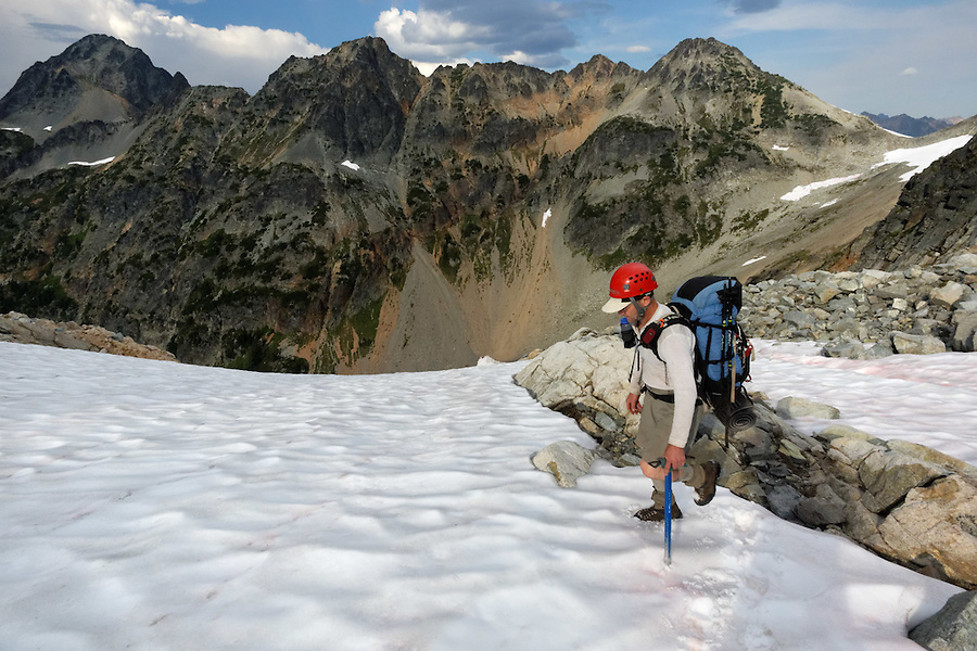Man hiking on snow field above Fisher River Basin near Fisher Lakes, North Cascades National Park, Skagit County, Washington, USA