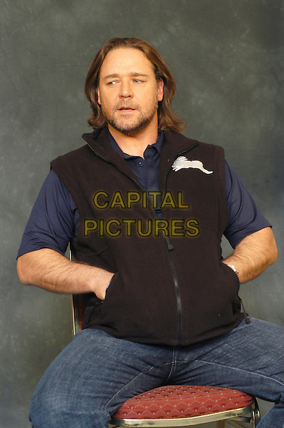 "RUSSELL CROWE.Photocall for ""3:10 To Yuma"", Rome, Italy..October 16th, 2007.three ten 310 3 10 half length black sleeveless top blue t tee shirt hands in pockets sitting stubble facial hair .CAP/CAV.©Luca Cavallari/Capital Pictures."