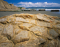 Point Reyes National Seashore, CA<br /> Detail patterned sandstone boulder on Drakes Beach with high cliffs in the background