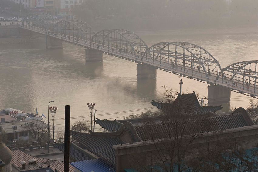 Lanzhou, the oldest bridge crossing the Yellow River in the fog of pollution. A chimney of individual heating is in activity in the foreground. <br /> <br /> -----<br /> Lanzhou, in the Gansu province is the most polluted city of China and in the world's top ten for atmospheric pollution due to human activity. The town is situated between two hills along the Yellow River and the polluted clouds remain blocked over the town. The sky is most of the time hidden by the pollution.