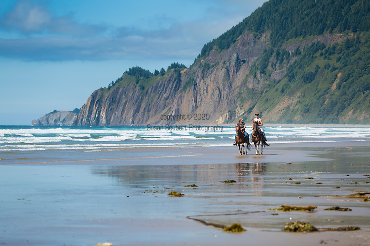 """Neahkahnie Beach in Manzanita, Oregon, a small beach town located in Tillamook County on the Northern Oregon coast.  Manzanita means """"little apple"""" in Spanish.  Neahkahnie Mountain is located at the north end of the 7 mile long beach.  Friends go for a horseback ride on the beach."""