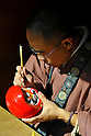 March 3, 2012, Tokyo, Japan - A Buddhist priest drew an eye on a Daruma doll, a Japanese traditional ornament of Buddhism, as begging of this year's happiness at Daruma Ichi, or Daruma Market, at Jindaiji Temple in Chofu, Tokyo, Japan on March 3, 2012. This was one of the biggest three Daruma Markets in Japan. Since it was taken place on March 3 and 4 every year no matter what day of the week and was weekend this year, many people showed up. (Photo by Koichiro Suzuki/AFLO) [4012]
