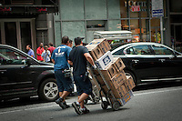 A man delivers boxes of Corona Extra on Times Square in the New York City borough of Manhattan, NY, Tuesday August 2, 2011. Corona Extra, better known as Corona and labeled as Coronita in Spain, is a brand of pale lager owned and produced by Cerveceria Modelo at a number of breweries in Mexico.