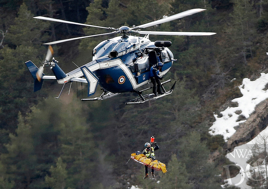A rescue worker is lifted into an helicopter near the crash site near Seyne-les-Alpes, France, Thursday, March 26, 2015. The co-pilot of the Germanwings jet barricaded himself in the cockpit and ÏintentionallyÓ rammed the plane full speed into the French Alps, ignoring the captainÌs frantic pounding on the cockpit door and the screams of terror from passengers, a prosecutor said Thursday. In a split second, he killed all 150 people aboard the plane. (AP Photo/Laurent Cipriani)
