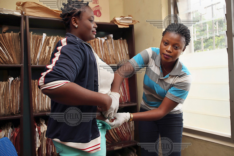 Abiodun Adetunji, a Planned Parenthood Federation of Nigeria (PPFN) Community Health Worker (CHEW), gives a Sayana Press contraceptive injectable to a young client at the PPFN clinic.