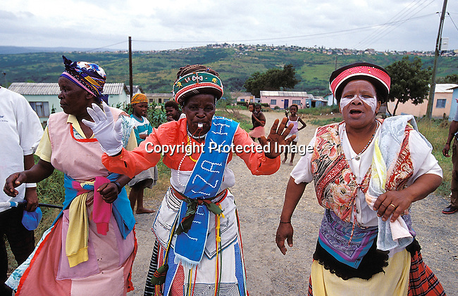 CUINITI02130.Culture. Initiation. Circumcision. Eastern Cape. Near King William's Town. Celebration before circumcision ceremony. Xhosa women wearing traditional dress, singing and dancing. Whistle, powerlines, hills, houses, headgear..©Per-Anders Pettersson/iAfrika Photos.