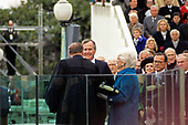 United States President George H.W. Bush is sworn-in as 41st President of the United States by Chief Justice William Rehnquist at the US Capitol on January 20, 1989.  First lady Barbara Bush (wearing a blue coat) looks on while holding the family bible.  Recognizable members of Congress at right include US Senator Ted Stevens (Republican of Alaska), US Senator Alan Simpson (Republican of Wyoming), and Speaker of the US House of Representatives Jim Wright (Democrat of Texas).<br /> Credit: Ron Sachs / CNP