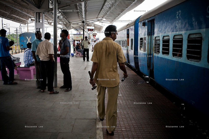 A train mechanic inspects the car attachments at Erode Junction stn., a 20 minute stop for the Himsagar Express 6318 in Tamil Nadu on 9th July 2009.. .6318 / Himsagar Express, India's longest single train journey, spanning 3720 kms, going from the mountains (Hima) to the seas (Sagar), from Jammu and Kashmir state of the Indian Himalayas to Kanyakumari, which is the southern most tip of India...Photo by Suzanne Lee / for The National