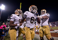 Running back Theo Riddick (6) celebrates his TD with quarterback Everett Golson (5) and center Braxston Cave (52).