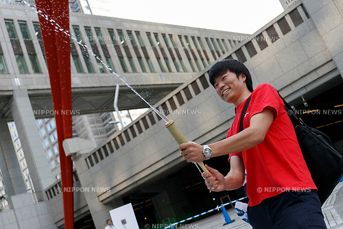A man enjoys sprinkling water during the Uchimizu-Biyori event outside the Tokyo Metropolitan Building on July 20, 2017, Tokyo, Japan. Uchimizu is a Japanese summer tradition of wetting down the streets by sprinkling water to keep down dust and cool pavements to reduce the temperature. (Photo by Rodrigo Reyes Marin/AFLO)