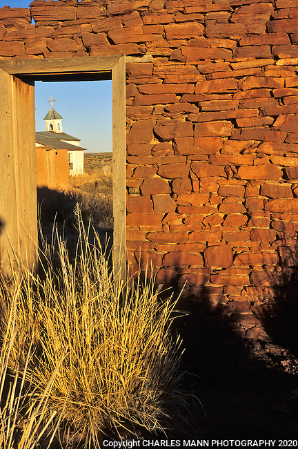 An old church tilts in the afternoon light near the ruined stone walls of nearby buildings at the abandonded village of Guadalupe, New Mexico, on the banks of the Pecos River near Fort Sumner.